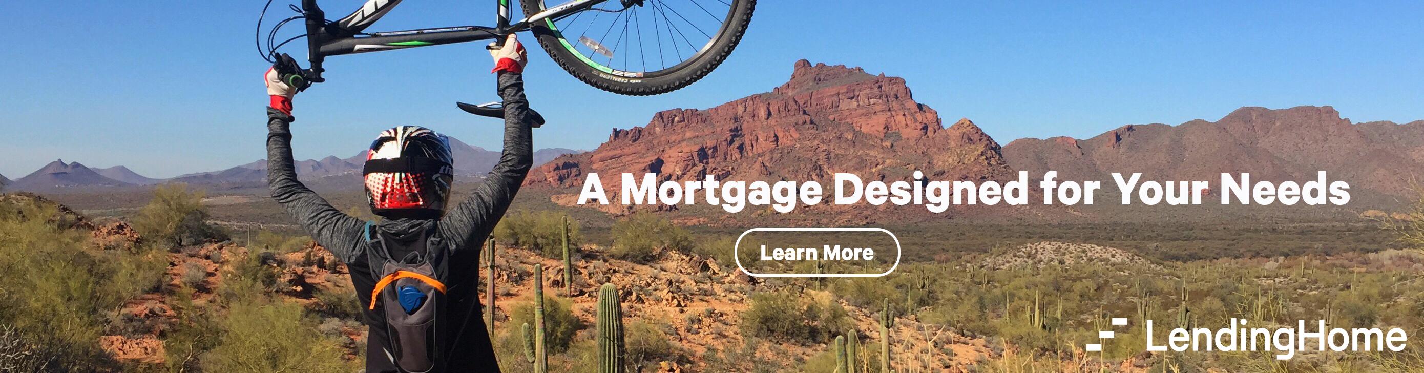 A man in a helmet raising his bike up to a desert landscape.